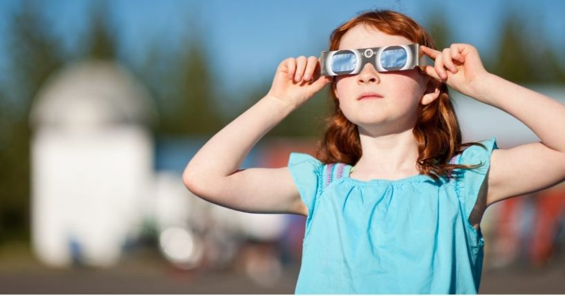 A young girl watches the annular solar eclipse with special viewing glasses.